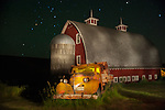 Old red barn and orange tractor at night