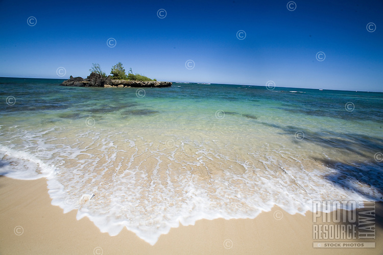Beach scene at a deserted North Shore beach with a small offshore island in clear blue water