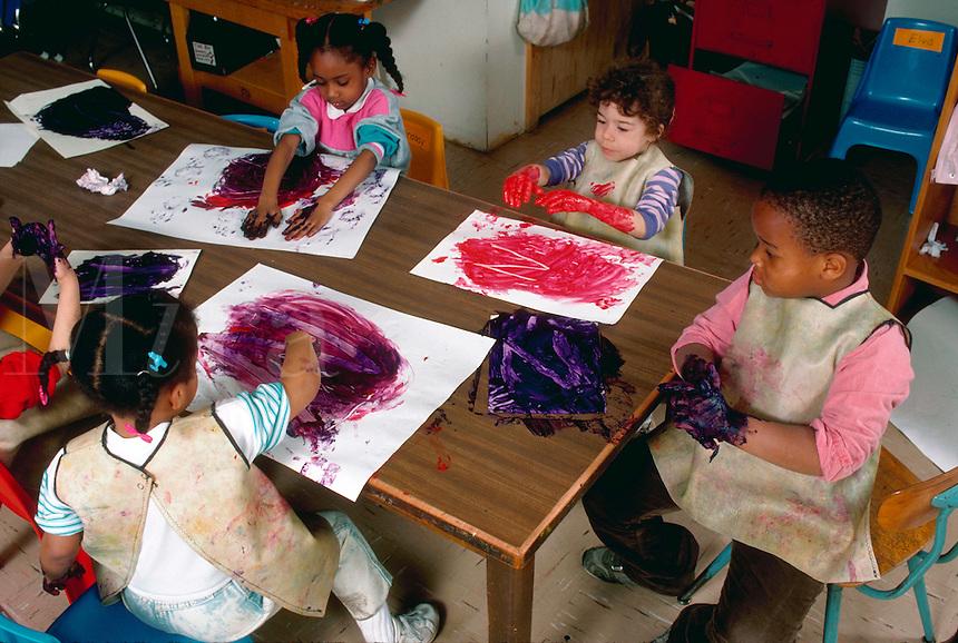 Preschoolers fingerpainting in a classroom.