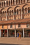 Two girls walk by the Romanesque Cathedral (side) in the Piazza Trento e Trieste; one girl wears a Laurel Wreath, worn in Italy by students after a graduation ceremony, a tradition originating at the University of Padua