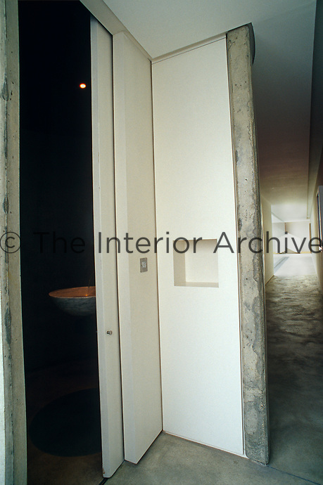 Glimpse through a sliding door from a concrete corridor into a downstairs loo