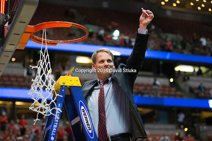 Wisconsin Badgers assistant coach Gary Close cuts down a piece of the net after the Western Regional Final NCAA college basketball tournament game against the Arizona Wildcats Saturday, March 29, 2014 in Anaheim, California. The Badgers won 64-63 (OT). (Photo by David Stluka)