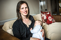 Portrait of a young woman breastfeeding her baby at home while sitting on  sofa in her living room.<br /> <br /> 15/05/2012<br /> Hampshire, England, UK