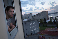 Borja by his window at dusk. He struggled for years to find work and sees joining the navy as a last resort solution to his problems. But competition is steep, with more than 40,000 people applying for 1,500 spots. Ferrol, Spain.