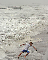 A boy runs from the Atlantic Ocean as high winds from Hurricane Isabel brought 10 foot waves September 18, 2003 in Ventnor, New Jersey. Hurricane Isabel brought high winds and heavy surf to the New Jersey coast. (Photo by William Thomas Cain/photodx.com) .
