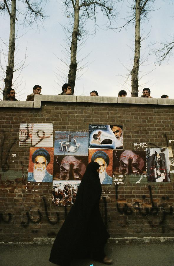 TEHRAN, IRAN - NOVEMBER 1979: A woman passing by the occupied U.S. embassy with the posters of the religious leader of the 1979 Iranian revolution; Ruhollah Musavi Khomeini on it's wall, during the hostage crisis. The crisis was a diplomatic crisis between Iran and the United States where 52 U.S. diplomats were held hostage for 444 days from November 4, 1979 to January 20, 1981, after a group of Islamist students took over the American embassy in support of the Iranian revolution. (Photo by Reza/Webistan).<br /> T&eacute;h&eacute;ran, Iran - Novembre 1979. Une femme passe devant l'ambassade des Etats Unis occup&eacute;e, avec, sur les murs ext&eacute;rieurs, des portraits du chef religieux de la r&eacute;volution iranienne de 1979 : Ruhollah Musavi Khomeini, pendant la crise des otages. La crise des otages &agrave; T&eacute;h&eacute;ran fut une crise diplomatique entre l'Iran et les Etats Unis durant laquelle 52 diplomates am&eacute;ricains furent pris en otage par un groupe d'&eacute;tudiants islamistes apr&egrave;s qu'ils se soient empar&eacute;s de  l'ambassade am&eacute;ricaine dans le cadre de leur soutien &agrave; la r&eacute;volution islamique. Les otages rest&egrave;rent  prisonniers pendant 444 jours du 4 novembre 1979 au 20 janvier 1981 (Photo de Reza/Webistan).