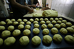 Palestinians prepare traditional date-filled mini cakes to sell for customers ahead of Eid al-Fitr holiday in the West Bank city of Nablus on June 14, 2018. Eid al-Fitr marks the end of Muslim's holy fasting month of Ramadan when faithfuls abstain from eating, drinking, smoking and sexual activities from dawn to dusk. Photo by Shadi Jarar'ah