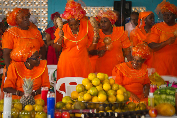 Shouter Baptist Day women dressed in bright orange African dress worshipping and playing maracas - double exposure