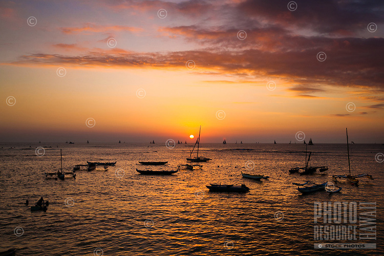 Sunset in front of the Outrigger Canoe Club, with surfers, kayaks and boats in the foreground, Waikiki, O'ahu.