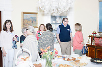 People gather around the food table after Democratic presidential candidate and South Bend mayor Pete Buttigieg spoke at a house party with the Bedford Democrats in Bedford, New Hampshire, on Sat., Apr. 20, 2019. The candidate stood on a chair throughout his speech.