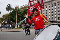 A boy plays a drum while people take part in march during May Day celebrations in Buenos Aires, Argentina on May 1, 2013. Photo by Juan Gabriel Lopera / VIEWpress.