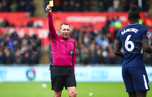 17th March 2018, Liberty Stadium, Swansea, Wales; FA Cup football, quarter-final, Swansea City versus Tottenham Hotspur; Referee Kevin Friend gives Davinson Sanchez of Tottenham Hotspur a yellow card during the 2nd half