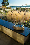 A small stone birdbath reflects the seedpods in this fall garden scene