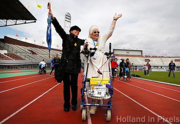 Rollatorloop in het Olympisch Stadion in Amsterdam. Wandelevenement  voor ouderen met een rollator. Een non legt lachend het parcours af, samen met een verzorgster