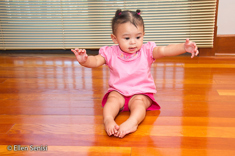 MR / Schenectady, NY. Infant (girl, 7 months, African American & Caucasian) exhibits 7-month-old human development milestone behavior as she uses hands to balance herself while sitting unsupported on floor. MR: Dal4. ID: AL-HD. © Ellen B. Senisi