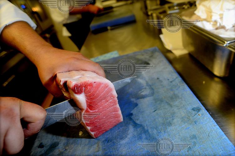 Chef Antonio Saez cuts fresh tuna steaks in the Lasarte Restaurant on Mallorca Street. /Felix Features