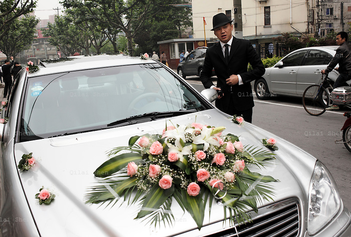 Coca Dai meets the florist and chauffeur before picking up his bride in a rented Mercedes Benz in Shanghai, China on 23 May 2009.   A hip street artist and a recent Catholic convert, Mr. Dai is one of many young Chinese embracing religion, perhaps to fill the lack of belief and ideology in an authoritarian communist China that embraces the most extreme form of capitalism in practice. The Chinese government and the Vatican have a long history of simmering mutual distrust and suspicion, as two parties compete for the control of the Chinese Catholic church, with some 15 million and growing number of faithfuls.  Overall Christians now number over 110 million in China, which makes it the third largest Christian nation in the world.