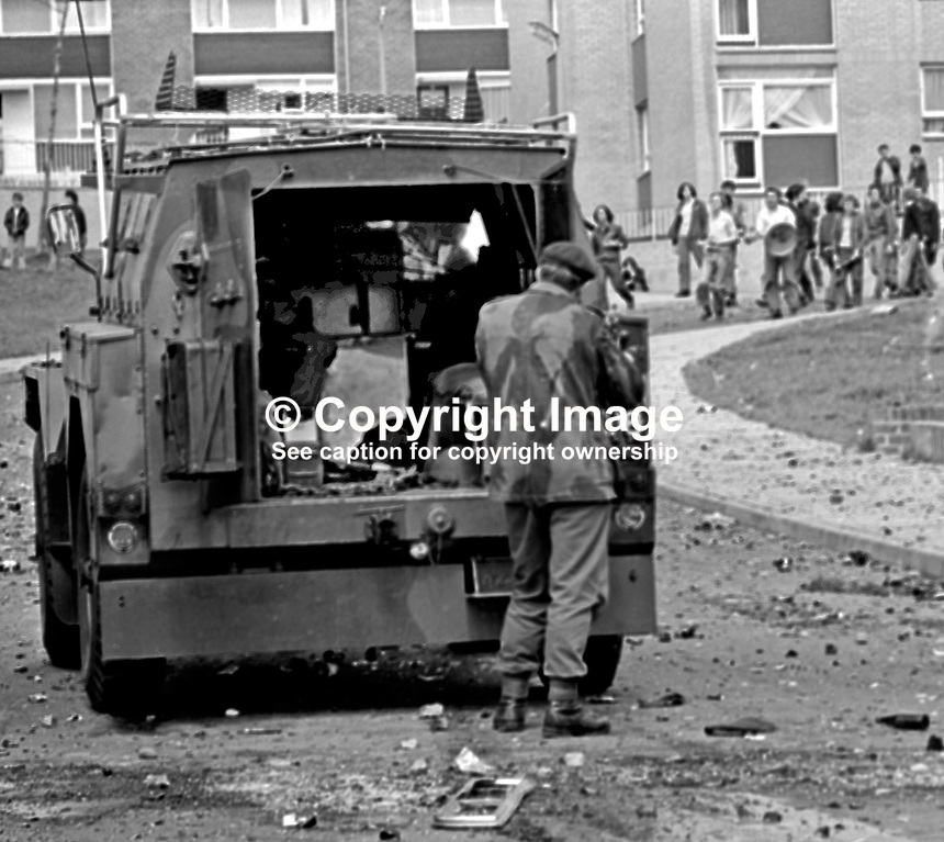 A British soldier shelters from rioters' missiles behind an armoured personnel carrier in the Lenadoon Avenue area, of Belfast, N Ireland, UK,  during widespread disturbances which followed the introduction of internment without trial. 387/71, 197108000387d...Copyright Image from Victor Patterson, 54 Dorchester Park, Belfast, UK, BT9 6RJ..Tel: +44 28 9066 1296.Mob: +44 7802 353836.Voicemail +44 20 8816 7153.Skype: victorpattersonbelfast.Email: victorpatterson@mac.com.Email: victorpatterson@ireland.com (back-up)..IMPORTANT: If you wish to use this image or any other of my images please go to www.victorpatterson.com and click on the Terms & Conditions. Then contact me by email or phone with the reference number(s) of the image(s) concerned.