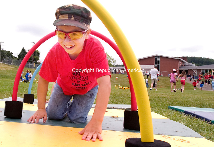 THOMASTON, CT. 15 June 2010-061510SV01--Michael Hycko, 8, crawls through an obstacle during field day at Black Rock School in Thomaston Monday. The whole school participated about 362 students.<br /> Steven Valenti Republican-American
