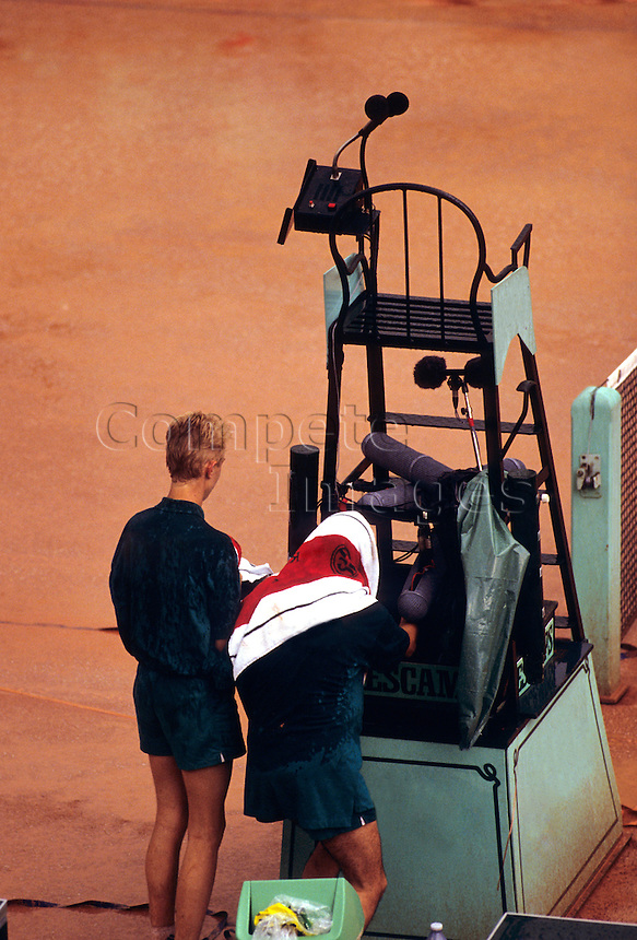 Ballboy and ballgirl standing next to umpires chair on clay court