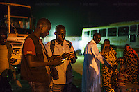 AGADEZ, NIGER &mdash; <br /> Two migrants from Burkina Faso exchange telephone numbers upon arriving to Agadez, Niger. This is the final stop of commercial buses. The journey from here on will be through the help of a network of smugglers who drive small pick-up trucks through the Sahara desert on their way to Libya.