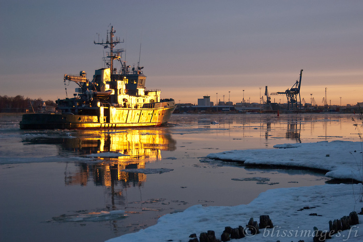 Tursas, a Finnish Coast Guard (Rajavartiolaitos) Ship turns golden approaching Turku harbour at sunrise.