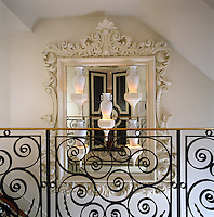 A collection of white ceramic vases is displayed against a mirror in an ornate plasterwork frame on the staircase landing
