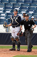 Tampa Yankees catcher Peter O'Brien (24) and umpire Jordan Albarado watch a fly ball during a game against the Daytona Cubs on April 13, 2014 at George M. Steinbrenner Field in Tampa, Florida.  Tampa defeated Daytona 7-3.  (Mike Janes/Four Seam Images)