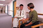 doctor discussing diagnosis and comforting woman in hospital hallway