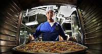 080809-N-7981E-082 North Arabian Sea (August 9, 2008)- Supply Department S-2 Division Sailor Culinary Specialist 3rd Class Gabriel Common, of Basile,  La., takes pizzas out of the oven in the aft galley aboard Nimitz-class aircraft carrier USS Abraham Lincoln (CVN 72). Lincoln is deployed to the U.S. 5th Fleet area of operations to support Operations Iraqi Freedom and Enduring Freedom as well as Maritime Security Operations (MSO). Operations in the 5th Fleet area of responsibility are focused on reassuring regional partners of the United States' commitment to security, which promotes stability and global prosperity. U.S. Navy photo by Mass Communication Specialist 2nd Class James R. Evans (RELEASED)