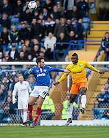 Aaron Pierre of Wycombe Wanderers heads clear of Marc McNulty of Portsmouth during the Sky Bet League 2 match between Portsmouth and Wycombe Wanderers at Fratton Park, Portsmouth, England on 23 April 2016. Photo by Andy Rowland.