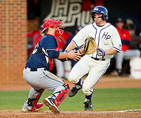 Liberty Flames catcher Trey Wimmer (10) waits for the baseball as Ryan Retz (34) of the High Point Panthers begins his slide into home plate at Willard Stadium on March 23, 2013 in High Point, North Carolina.  The Panthers defeated the Flames 9-3.  (Brian Westerholt/Four Seam Images)
