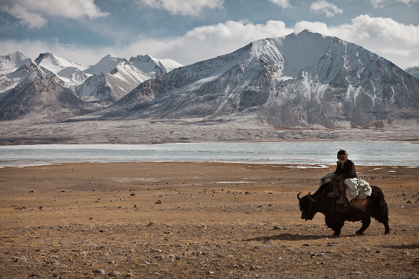 A Kyrgyz riding the leading yak of a caravan beside the frozen Chaqmaqtin lake..From Ak Chyktash (Mullah Abdul Kossim) to Ech Keli (Er Ali Boi's camp). .Trekking with yak caravan through the Little Pamir where the Afghan Kyrgyz community live all year, on the borders of China, Tajikistan and Pakistan.