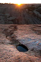 "Enchanted Rock sunset with runoff.  Taken just as the sun drops over the ""Little Rock"" to the west of the main dome one spring evening."