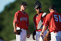 Batavia Muckdogs starting pitcher Martin Anderson (49) and catcher Pablo Garcia (4) wait for pitching coach Jason Erickson (51) on the mound during a game against the West Virginia Black Bears on July 3, 2018 at Dwyer Stadium in Batavia, New York.  Batavia defeated West Virginia 5-4.  (Mike Janes/Four Seam Images)