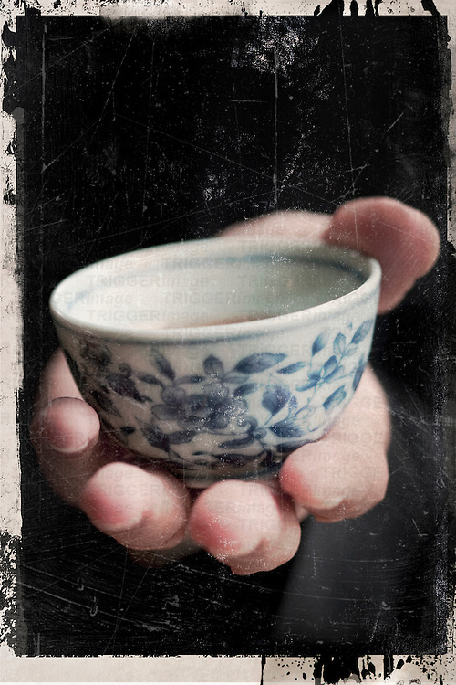 A hand holding an asian tea cup with floral pattern