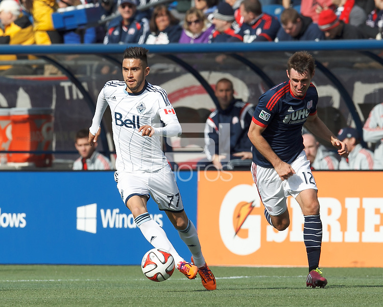 Vancouver Whitecaps FC substitute midfielder Pedro Morales (77) dribbles as New England Revolution midfielder Andy Dorman (12) closes. In a Major League Soccer (MLS) match, the New England Revolution (blue/white) tied Vancouver Whitecaps FC (white), 0-0, at Gillette Stadium on March 22, 2014.