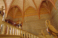 Trompe l'oeil stone walls and a rib vaulted ceiling covered in hand-painted motifs dominate the main staircase