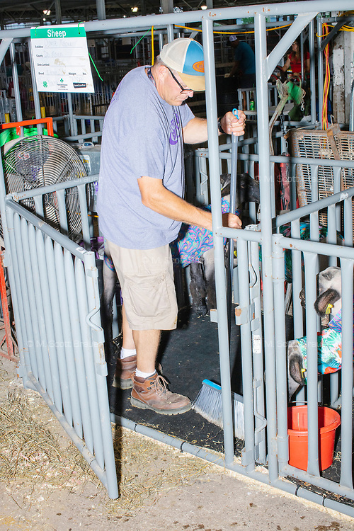 A man cleans a sheep pen in the Sheep Barn at the Iowa State Fair in Des, Moines, Iowa, on Sun., Aug. 11, 2019.