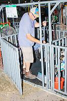 A man cleans a sheep pen in the Sheep Barn at the Iowa State Fair in Des, Moines, Iowa, on Sun., Aug. 11, 2019.