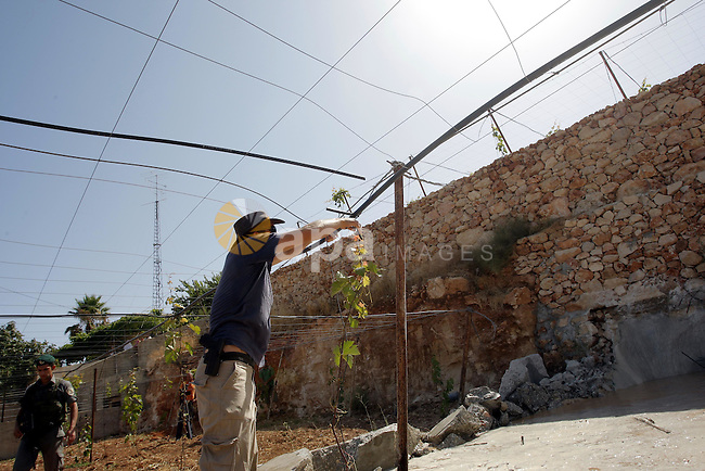 Israeli border police officers stand guard as construction vehicles destroy a man-made reservoir on a Palestinian farm near the West Bank  city of Hebron on 14 July 2010. According to a spokesperson for Israel's Civil Administration, the reservoir was destroyed as part of a routine law enforcement operation aimed at curbing the theft of water from surrounding communities. Photo by Mamoun Wazwaz