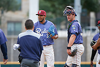 Frisco RoughRiders pitcher Esmerling Vasquez (35) and catcher Alex Kowalczyk (27) look to athletic trainer Alex Rodriguez during a Texas League game against the Midland RockHounds on May 21, 2019 at Dr Pepper Ballpark in Frisco, Texas.  (Mike Augustin/Four Seam Images)