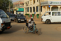NIGER Niamey, handicapped person with wheelchair on the road between traffic