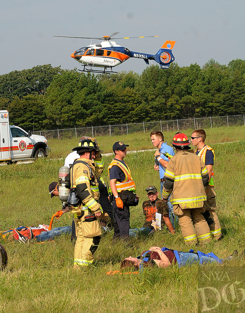 STAFF PHOTO FLIP PUTTHOFF <br /> A medical helicopter lands at the Rogers airport while firefighters and ambulance personnel treat mock victims during an airplane-crash drill on Tuesday Sept. 9 2014 at the Rogers airport.
