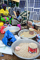 BURKINA FASO, Provinz Poni, Gaoua, weekly market with food crops and solar panels, girl playing with mobile phone /Gaoua, Markt, Verkauf Erdnuesse, Bohnen, Reis, Stand mit Solar Modulen, Maedchen mit Mobiltelefon