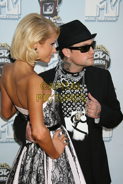 PARIS HILTON & BENJI MADDEN.Arrivals - 2008 MTV Movie Awards held at Gibson Amphitheatre, Universal City, California, USA, 01 June 2008..half length strapless tanned black lace earrings dress hat sunglasses ray bans couple hand tattoos back .CAP/ADM/MJ.©Michael Jade/Admedia/Capital Pictures