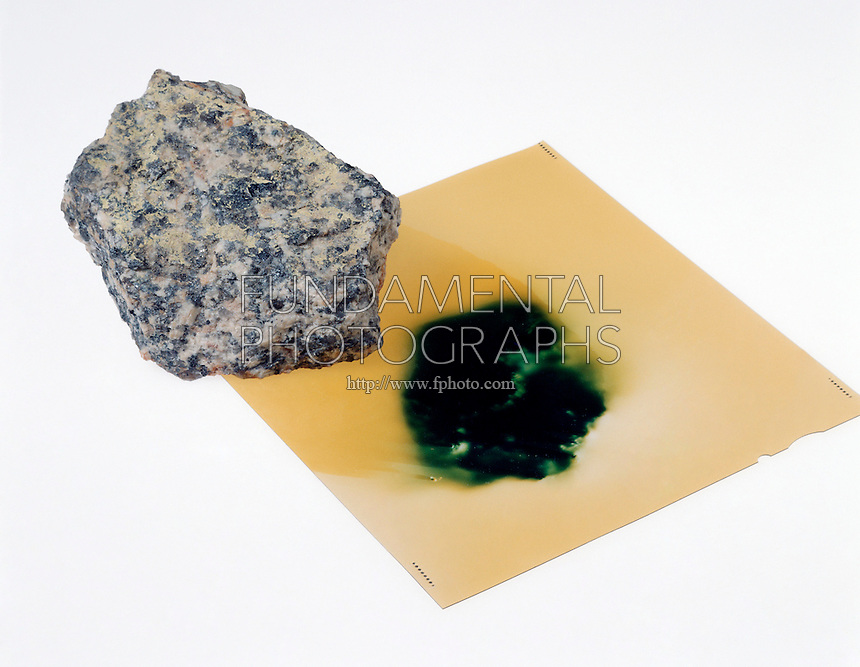RADIOACTIVITY: EFFECT OF URANIUM ORE ON FILM<br /> Film Is Exposed To Radioactivity Of The Ore<br /> After exposure the film is processed showing a dark spot where the radioactive waves emitted from the ore.