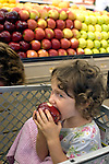 Berkeley CA Girl, three-years-old sampling nutritious apple while grocery shopping with mother MR