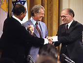 United States President Jimmy Carter, center, President Anwar Sadat of Egypt, left, and Prime Minister Menahem Begin of Israel, right, share a 3-way handshake during the signing ceremony for the Camp David Accords in the East Room of the White House in Washington, D.C. on September 17, 1978..Credit: Arnie Sachs / CNP