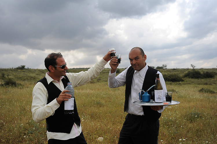 Protesters act as two businessmen who drink wine made of oil, at Adolam Park, Israel. Environmental organizations protest against IEI's plan to drill the region searching for shale oil.
